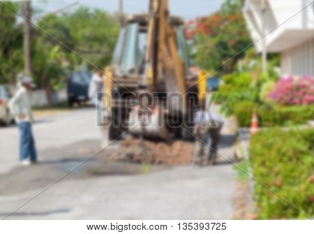 Blur blurred Plumbing Repair Man and excavator scoop digging,  Worker using a small tracked excavator to dig a hole to fix a water on the road, and soft-focus background.