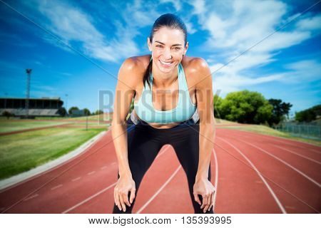 Sportswoman posing his hands on knee against high angle view of track