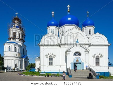 BOGOLUBOVO RUSSIA - AUGUST 21 2015: Unidentified people visit Cathedral of Bogolyubsk Icon of Our Lady Gate Assumption Church with bell tower of St. Bogolyubsky monastery Vladimir region Russia