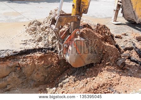 Excavator working on the Repair of pipe water and sewerage on road Worker using a small excavator to dig a hole to fix a water. (select focus on excavator)