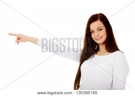 Smiling young woman shows something