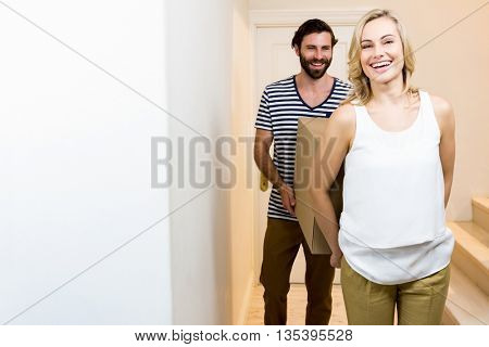 Young couple carrying card board boxes in their new house