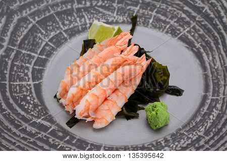 Japanese Cuisine. Sushi. Shrimp Sashimi On A Round Plate With Lime And Wasabi