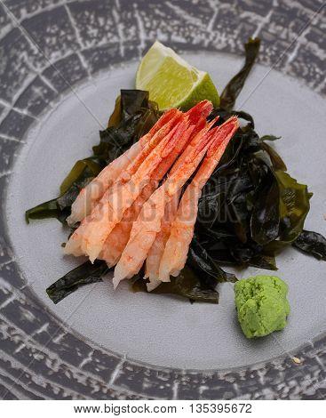 Japanese Cuisine. Sushi. Shrimp Sashimi On A Round Plate With Lime And Wasabi