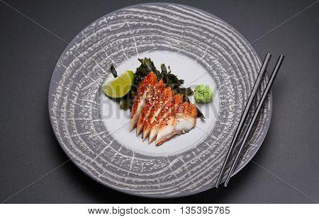 Japanese Cuisine. Sushi. Eel  Sashimi On A Round Plate