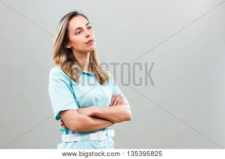 Worried nurse looking away and thinking about something.