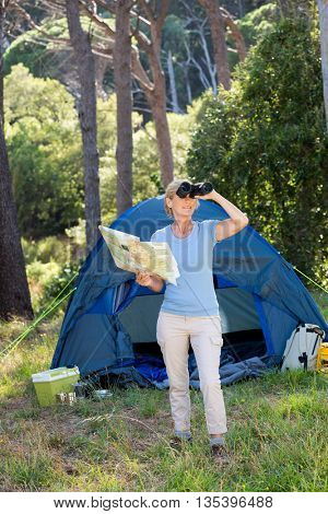 Mature woman looking on binoculars on camp site