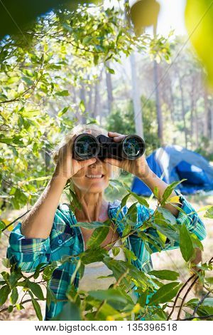 Mature woman smiling and looking on binoculars on the wood