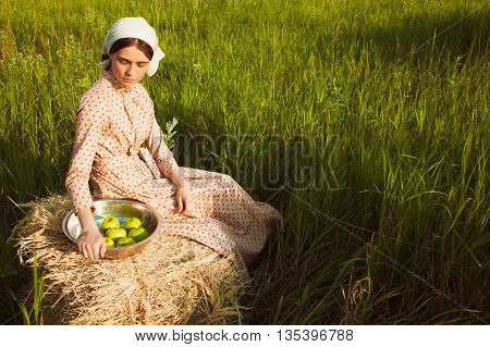 The healthy rural life. The woman in scarf sitting on a haystack with apples against green meadow