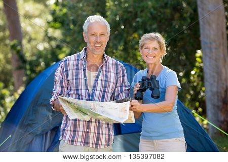 Mature couple smiling and holding binoculars and map on their camp site