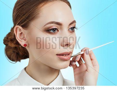 Hand of visagiste applying lipstick on female lips on the blue background