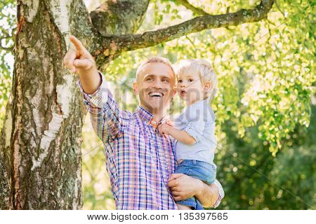 Young father with his son spending time in the park. Father pointing somewhere.