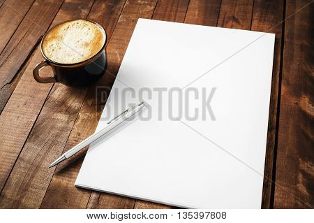 Blank letterhead coffee cup and pen on vintage wooden table background. Blank branding template. Photo of blank stationery. Mock-up for design portfolios.