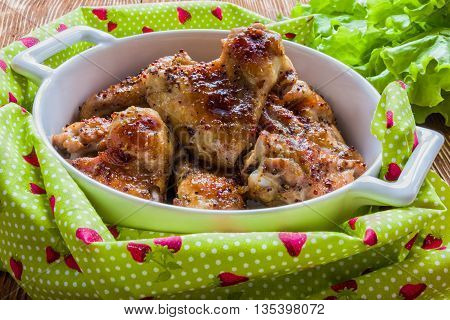 Roasted chicken wings in white baking dish. Cooked with sauce from mustard honey and soy sauce.
