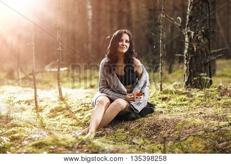 Young beautiful woman sitting in the forest. Enchantment and dreamy concept