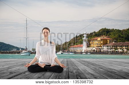 Young woman practicing yoga in the lotus position outdoors on the pier