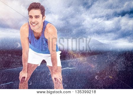 Male athlete standing with hand on knee against landscape with cloudy sky