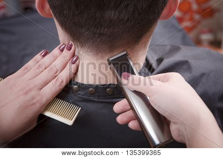 Man's hairstyling and haircutting with hair clipper in barber shop or hairdressing salon. Closeup picture.