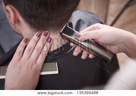 Handsome man having his hair cut in hairdressing salon or beauty salon. Hairdresser using hair clipper for man's hairstyling.