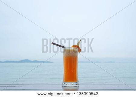 freshly squeezed orange juice in glass on outdoor wooden  table