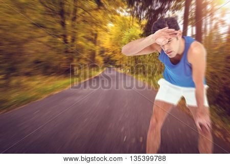 Tired athlete wiping his sweat with hand against country road along trees in the lush forest