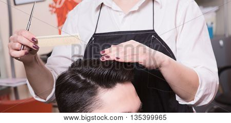 Closeup picture of hairdresser cutting handsome man's hair in hairdressing saloon. Handsome man in hairdresser's.
