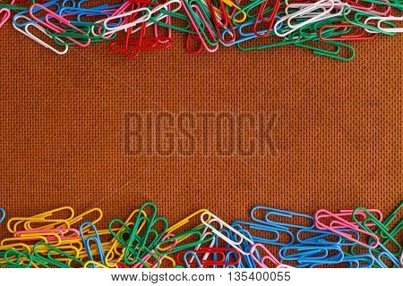 Bunch of colorful paper clips on wood background photo