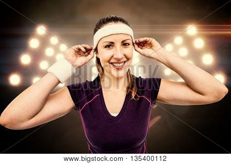 Female athlete wearing headband and wristband against digitally generated image of spotlight