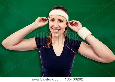 Female athlete wearing headband and wristband against green background