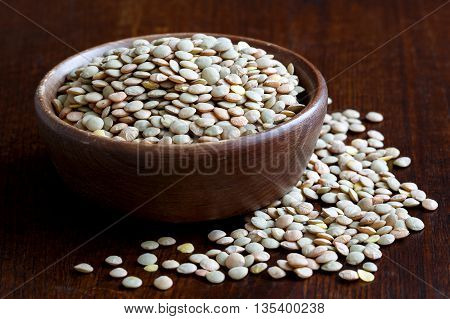 Rustic Bowl Of Green Uncooked Lentils Isolated On Dark Wood In Perspective. Spilled Lentils.