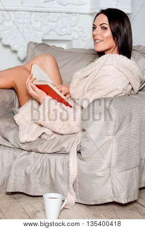 beautiful slim girl in the home beige bathrobe sitting in a beige easy chair reading a book and smiling