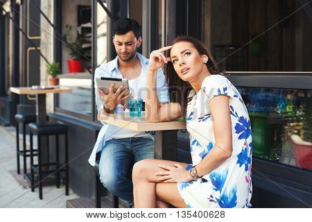 Bad date. Man having fun with digital tablet during a date with a beautiful woman.