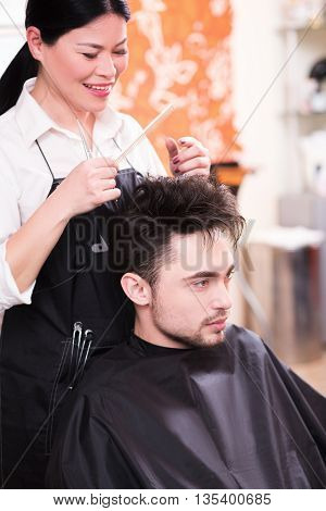 Beautiful young hairdresser working in hairdressing salon and making haircut for handsome man. Handsome man looking at mirror.