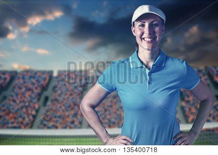 Sportswoman posing on black background against digital image of tennis field in a stadium