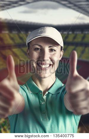 Sportswoman posing on black background against tennis field on a stadium