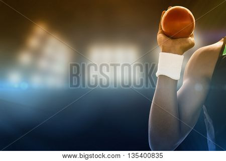 Close up of hand holding a shot against composite image of spotlight