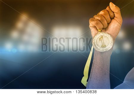 Athlete holding gold medal after victory against composite image of spotlight