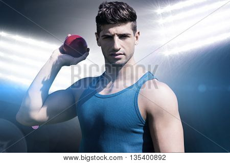 Front view of sportsman is posing and holding a shot against spotlights