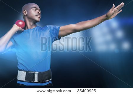 Front view of sportsman practising shot put against composite image of spotlight