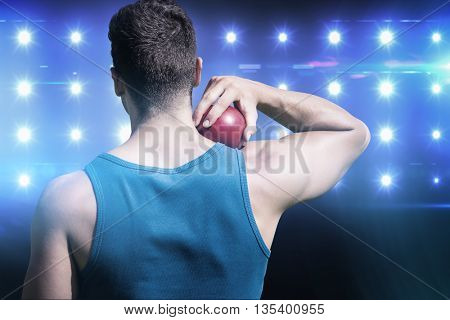 Rear view of sportsman practising shot put against composite image of blue spotlight