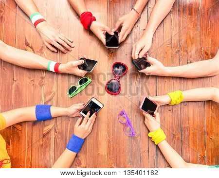 Many white hands using phone view from above - International people around wood table holding new mobile - Concept of modern technology addiction in everyday life -