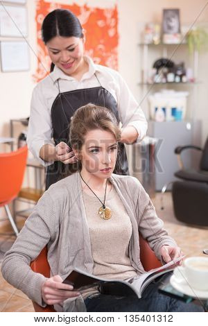 Beautiful lady reading magazine while having her hair cut or done by young beautiful barber girl in hairdressing saloon.