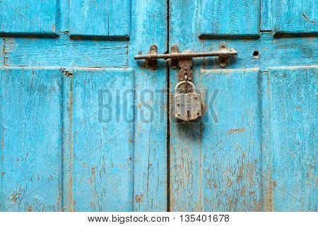 Padlock on a blue grungy door in Nepal