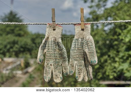 pair old work gloves and clothespin on rope