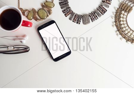 Office table top view shot with computer keyboard, coffee cup, earphone, spectacles, mobile phone with a blank white screen and ladies necklaces