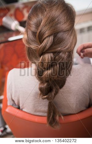 Beautiful lady having weave braids while sitting in hairdressing salon.