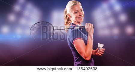 Badminton player holding racket and shuttlecock against composite image of spotlight