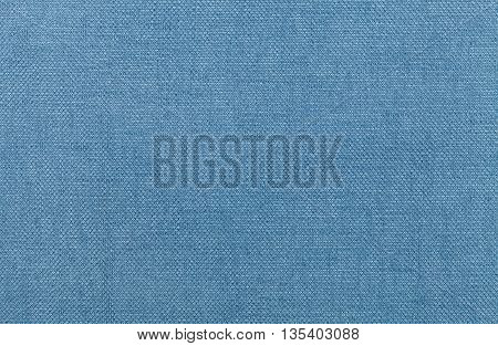Light blue background from a textile material. Fabric with natural texture. Cloth backdrop.