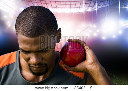 Portrait of sportsman practising shot put against american football arena