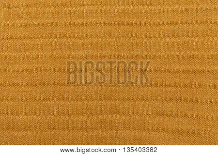 Dark orange ocher background from a textile material. Fabric with natural texture. Cloth backdrop.